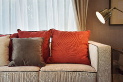 Red and brown pillows on beige sofa with a bras lamp Royalty Free Stock Images