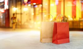 Red and brown shopping bags on floor front of mall. Red and brown shopping bags on floor front the mall store at night, business, retail, banner and sign concept Stock Photo