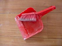Red brush and scoop on a wooden floor Stock Images