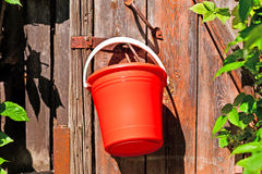 Red bucket. Hanging on the door Royalty Free Stock Image