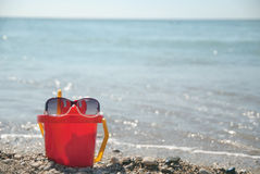 Red bucket. With sunglasses at the beach Royalty Free Stock Photography