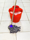 Red bucket with foamy water and mop the floor Royalty Free Stock Images