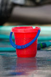 Red Bucket and Green Hose. Red Bucket with Blue Handle with Green Hose in Backgrund reflected against wet pavement Royalty Free Stock Photos