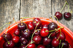 Red bucket scoured rural cherries on a wooden Royalty Free Stock Photography