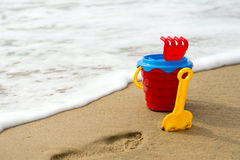 Red bucket with a shovel, a rake and a net on the beach Royalty Free Stock Photography