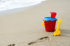 Red bucket with a shovel, a rake and a net on the beach Stock Photo