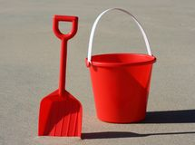 Red bucket and spade. A red plastic bucket and spade on the beach royalty free stock image