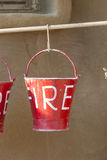 Red buckets filled with sand used as fire fighting equipment Stock Photos