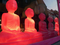 Red buddhas in shop window. Row of lighted red buddhas in shop window with urban buildings reflection Royalty Free Stock Images