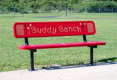 Red buddy bench on a playground. Red buddy bench on a school play ground. A bench for a shy or lonely child to sit on to indicate they need a friend or a buddy stock photography