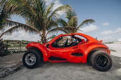 Red buggy parked under a palm tree. Mexico, Cancun, Cozumel, royalty free stock photo