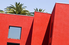 Red building. Modern red building detail with palm trees Stock Photo