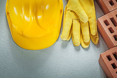 Red building bricks protective hard hat leather safety gloves on. Concrete surface construction concept Stock Images