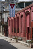 Red building and Cuban Flag. In Havana's backstreets Stock Photography
