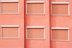 Red Building Facade with Six Closed Windows Shutters Royalty Free Stock Images