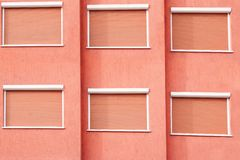 Red Building Facade with Six Closed Windows Shutters Royalty Free Stock Photos