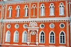 Red building facade. Variety of windows. Stock Photos