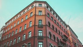 Red building of Stockholm, Sweden. Nordic apartment. On city square with blue sky stock video footage