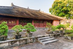 Red building at the Tu Duc Royal Tomb. Hue, Vietnam. Amazing red building at the Tu Duc Royal Tomb in Hue, Vietnam. Green Bonsai trees growing beside the stock photography