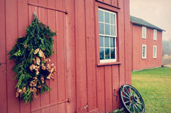 Red Building Wagon Wheel. A red barn like building with windows and a wagon wheel in front with some evergreen branches hanging on the doorway.  Located at Old Royalty Free Stock Photography