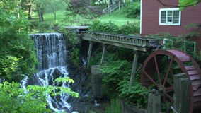 A red building with a water wheel and waterfall