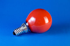 Red bulb on blue background Royalty Free Stock Photos