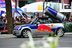 Red Bull mini cooper publicity car. With a can of red bull drink behind at the Red Bull Speed Street Singapore 2011 on 24 April 2011 at Orchard Road, Singapore Royalty Free Stock Image