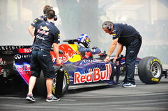 Red Bull Racing pit crews cooling F1 car. Red Bull Racing pit crews cooling the F1 RB6 car after David Coulthard performed donuts during Red Bull Speed Street royalty free stock photo