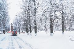 A red bulldozer cleans the streets after heavy natural snowfall. Getting ready for Christmas. Freezing day stock photography