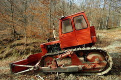Red bulldozer in the forest. In the forest. Red bulldozer, used  for easy access of forestry equipment in some mountain areas Stock Images