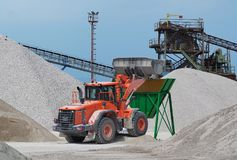 Red bulldozer at work on a green hopper under the conveyor belts in a gravel pit.  stock images