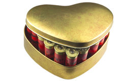 Red bullet shotgun cartridges in tin heart shape box. Gift for real man. Isolated on white background. Close up image. Horizontal shot Stock Photos