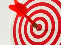 Red bullseye dart arrow hitting target center of dartboard. Concept of success, target, goal, achievement. Royalty Free Stock Photos