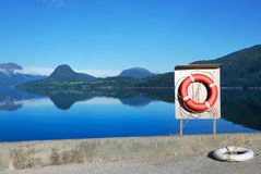 Red buoy against the blue view of fjord Royalty Free Stock Images