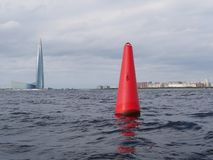 Red buoy and skyscrape. Baltic sea in autumn. royalty free stock images