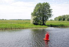 Red buoy beacon in lake shore water mark for ships Royalty Free Stock Photos
