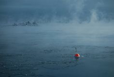 Red buoy in the freezing Baltic Sea in Helsinki, Finland Royalty Free Stock Image