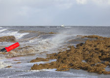 Red buoy is loose and thrashed against a dike Royalty Free Stock Photos