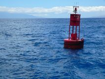 Red Buoy on Ocean. A red buoy marker bobbing in the deep blue ocean Royalty Free Stock Image