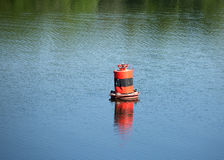 Red buoy on quiet river with resting on it ducks o Royalty Free Stock Photography