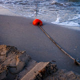 Red buoy on sand Stock Photos