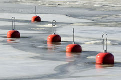 Red buoys in the frozen water Stock Photo