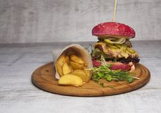 Red burger with meat and fried potatoes in pita bread stock image