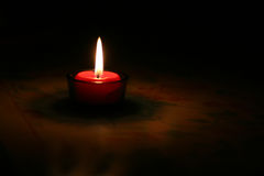 Red burning candle. Isolated red burning candle in shadows at night Royalty Free Stock Photos