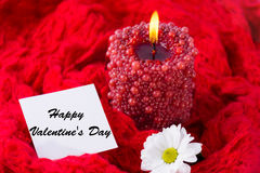 Red burning candle, chamomile, red scarf. Valentine`s Day. Red burning candle, chamomile, red scarf Royalty Free Stock Images