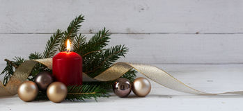 Red burning candle with christmas decoration, fir tree, baubles Stock Images