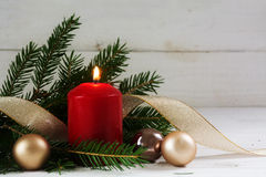 Red burning candle with christmas decoration, fir tree, baubles Stock Photo