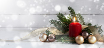 Red burning candle with christmas decoration, fir tree, baubles Stock Photos