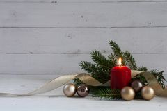 Red burning candle with christmas decoration, fir tree, baubles Royalty Free Stock Photography