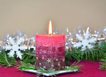 Red burning candle with Christmas decorations, fir branches Royalty Free Stock Photos